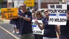 Supporters of officer Darren Wilson hold placards outside Barney's Sports Pub in St. Louis, Missouri